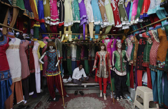 A vendor waits for customers at his shop selling clothes at a market in Mumbai.