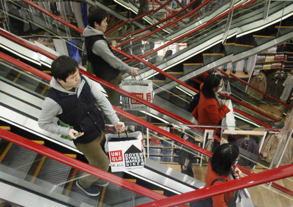 Shoppers stand on the escalator at Fast Retailing's new flagship Uniqlo store at Tokyo's Ginza district.