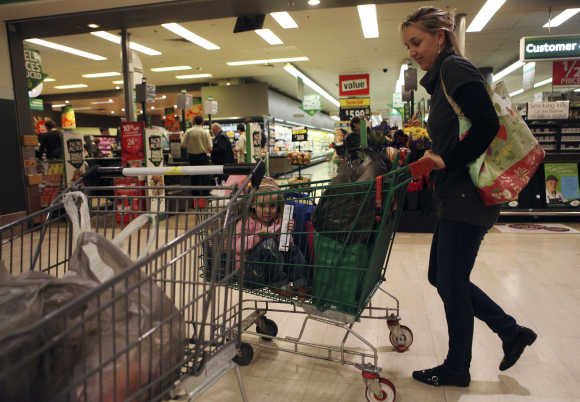 A customer leaves a Woolworths supermarket in Sydney.