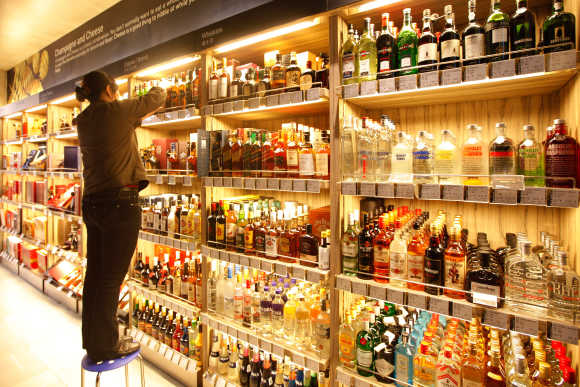 An employee arranges bottles of whisky at a supermarket in Shanghai.
