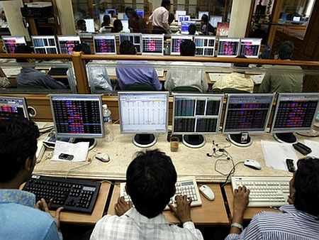 Indian brokers engage in trading on their computer terminals at a stock brokerage firm in Mumbai.