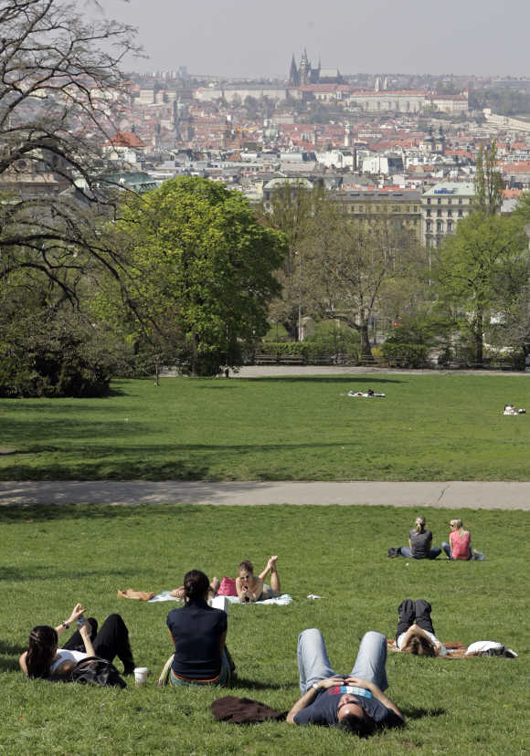 People enjoy a sunny day in a park in Prague.