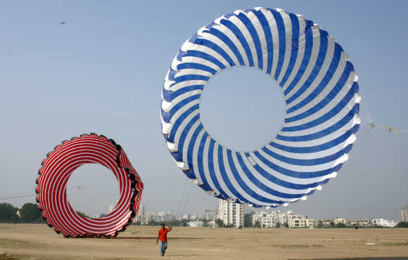 A kite-flying enthusiast tightens the strings of a kite during a practice session in Ahmedabad.