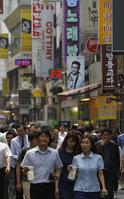 People walk at a shopping district in central Seoul.