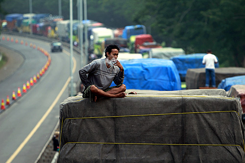 Driver Aditya Gumay smokes a cigarette on top of his truck while stuck in traffic, about 8 km (5 miles) from the port of Merak near Cilegon, Banten province.