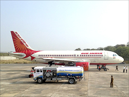 A Bharat Petroleum refuelling vehicle sits on the tarmac next to an Air India A320 aircraft.