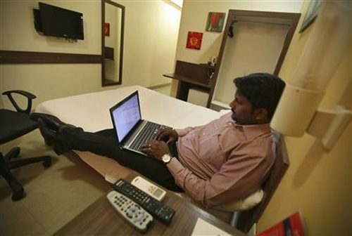 A guest works on a laptop inside his room at the Tata Group's Indian Hotels Co.