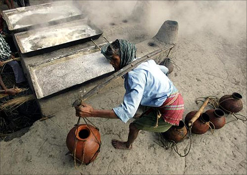 A labourer carries pots of palm juice to prepare jaggery, a form of candy, at a roadside factory in Bagnan, Kolkata.