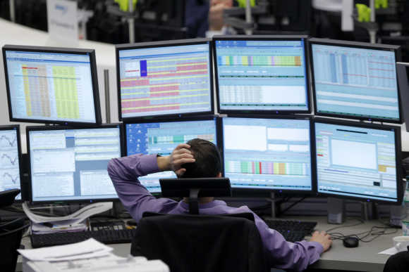 A trader watches screens at his desk at the Frankfurt stock exchange.
