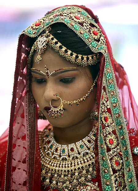 A bejeweled bride attends a mass marriage ceremony in Gujarat.