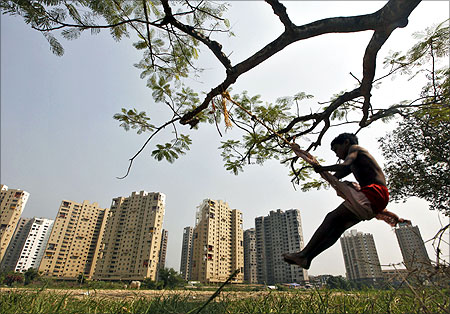 A boy plays on a swing suspended from a tree in front of a residential estate under construction in Kolkata.