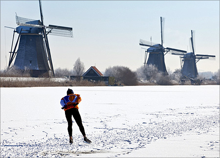 A lone skater skates past three windmills as he enjoys the first time he can skate on natural ice in Kinderdijk, near Rotterdam.