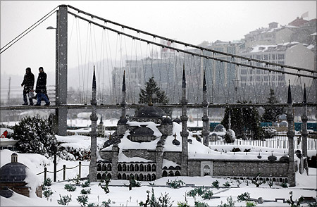 Visitors walk over a model of the Bosphorus bridge with the model of Ottoman-era Sultanahmet mosque in the foregorund at the snow-covered Miniaturk in Istanbul.