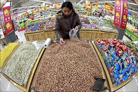 A customer chooses peanuts at a supermarket in Huaibei, Anhui province.