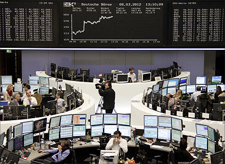 Traders are pictured at their desks in front of the DAX board at the Frankfurt stock exchange.