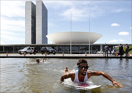 Brazilians use surfboards in the pond next to National Congress during a protest against the new Forestry Law being debated by the legislature in Brasilia.
