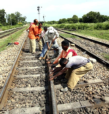 Railway labourers repair a railway track after it was damaged by protesters at Ghagwal.