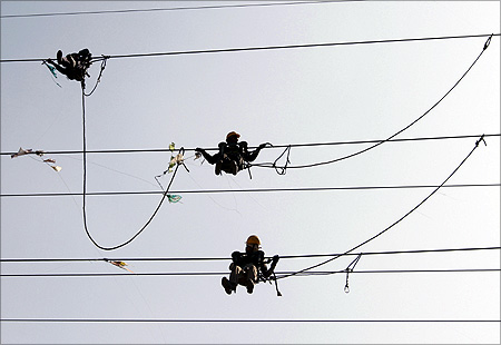 Labourers remove kites tangled up in electric power cables.
