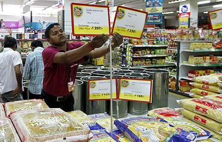 A worker of a food superstore arranges price tags of the products inside a mall in the western Indian city of Ahmedabad.