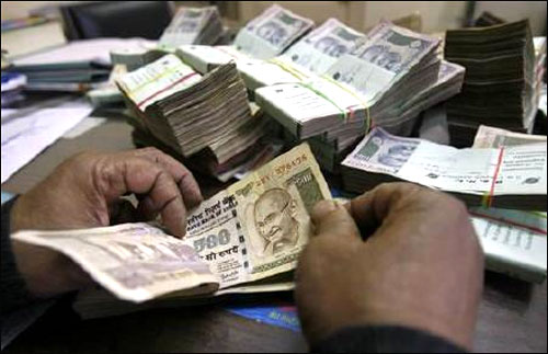 An employee counts rupee notes at a cash counter inside a bank in Agartala.