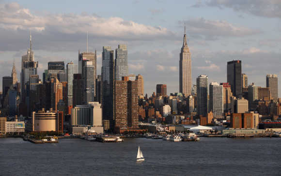 A boat sails in the Hudson River in front of the Empire State Building and the skyline of midtown Manhattan in New York.