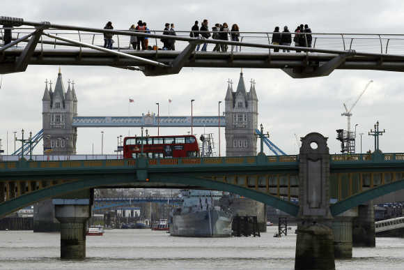 Pedestrians cross the Millenium Bridge spanning the Thames River in London.