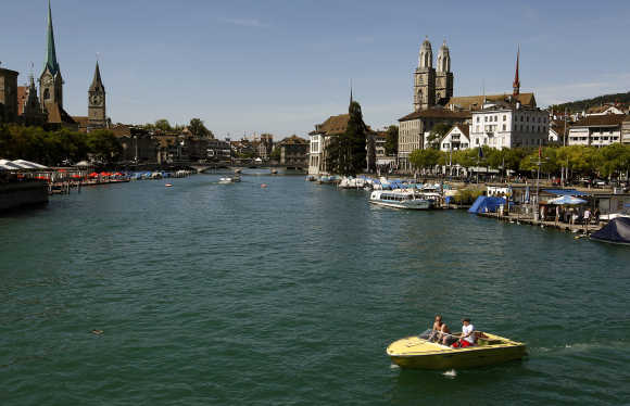 People sit in a boat on the Limmat River during sunny summer weather in Zurich