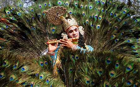 An artist dressed as Lord Krishna performs during a media preview of the 25th Surajkund Crafts Fair in the northern Indian state of Haryana