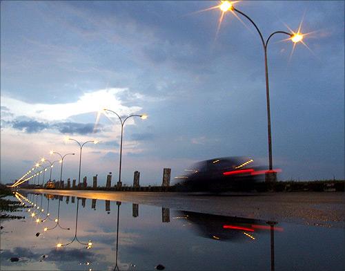 A car passes on a highway beneath pre-monsoon clouds in the eastern Indian city of Kolkata.