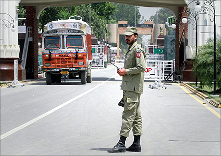A paramilitary soldier stands guard as a truck carrying wheat crosses into Pakistan from India, at the Wagah border.