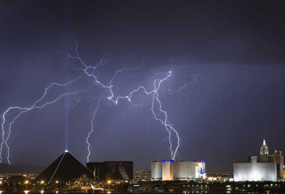 Lightning strikes behind the Luxor, left, and Excalibur, right, as a thunderstorm passes through Las Vegas.