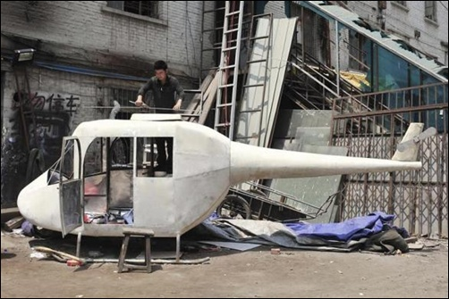 Gao Hanjie installs the rotor blades on his homemade helicopter in Shenyang, Liaoning province, China.