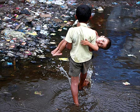 Ashfaq, 10, carries his two-year-old brother Farhaan through a flooded pathway in a Mumbai slum.