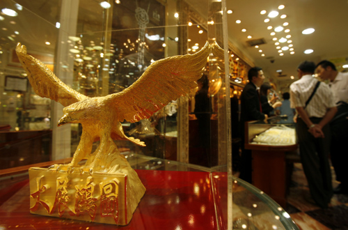 Visitors from mainland China tour a jewellery store displaying a hawk-shaped golden figurine.