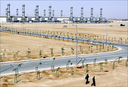 People walk near power plant number 10 at Saudi Electricity Company's Central Operation Area, south of Riyadh.