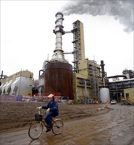 A worker rides his bike near Syncrude's $7.5 million expansion mine, which remains shut after residents complained of odors coming from the site, north of Fort McMurray, Alberta.