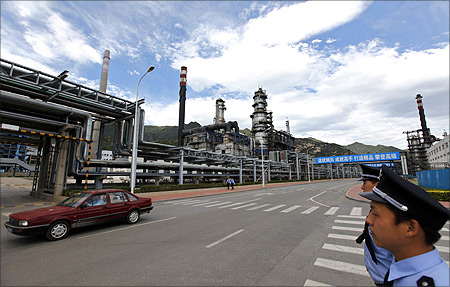 Security personnel stand guard as a car drives past the Yanshan oil refinery of Sinopec Corp. in Beijing.