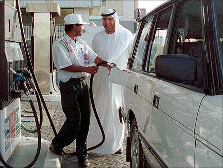 A car owner smiles as he chats to a petrol pump attendent while refilling his car at a Dubai petrol station.