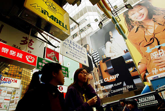 Shoppers are surrounded by advertisements at Hong Kong's Causeway Bay shopping district.