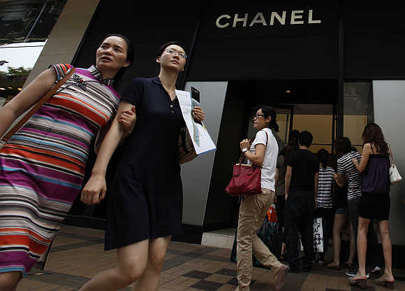 Mainland Chinese visitors walk past a Chanel store as others line up at Hong Kong's Tsim Sha Tsui district.
