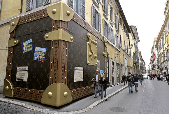 Tourists pass a Louis Vuitton shop closed for refurbishment, its facade covered with a faux suitcase, in Rome.
