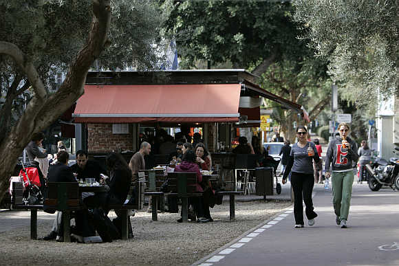 People walk past a cafe in Tel Aviv.