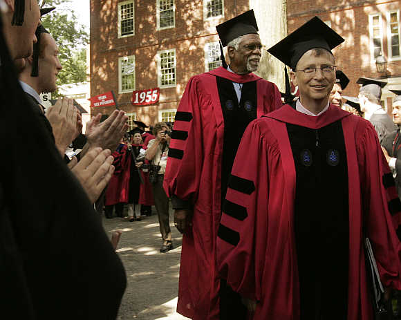 Honorary degree recipient Bill Gates walks past graduating students during Commencement Exercises at Harvard University in Cambridge.