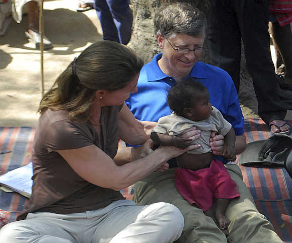 Bill Gates and wife Melinda hold a child during their visit to a Danapur slum area in Patna.