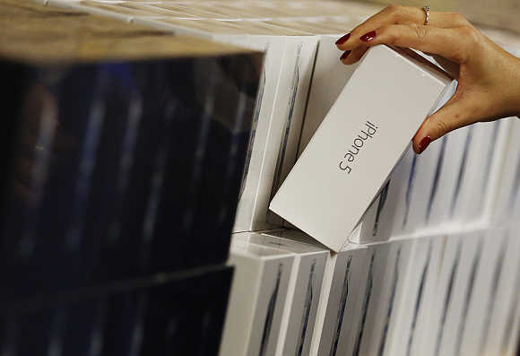 A store worker picks up an Apple iPhone 5 in London.