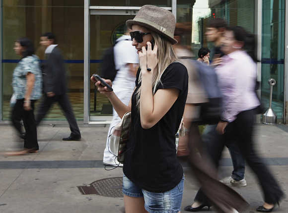 A woman uses mobile phones as she talks, writes a message and listens to music at the financial centre of Sao Paulo.