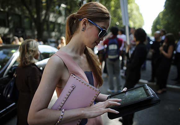 A woman looks at her tablet in Milan.