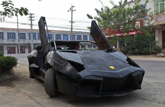 A friend of Wang Jian sits in a hand-made replica of a Lamborghini Reventon in Suqian, Jiangsu province, China. Wang, a young farmer who worked at a garage for more than a decade, built the replica of a Lamborghini Reventon with a second-hand Nissan and Santana. The self-made roadster cost Wang around 60,000 RMB ($9,450) and can reach a maximum speed of 160mph.