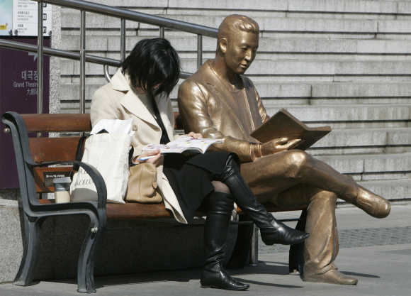 A woman reads a book beside a bronze statue in front of Sejong Centre for the Performing Arts in central Seoul.