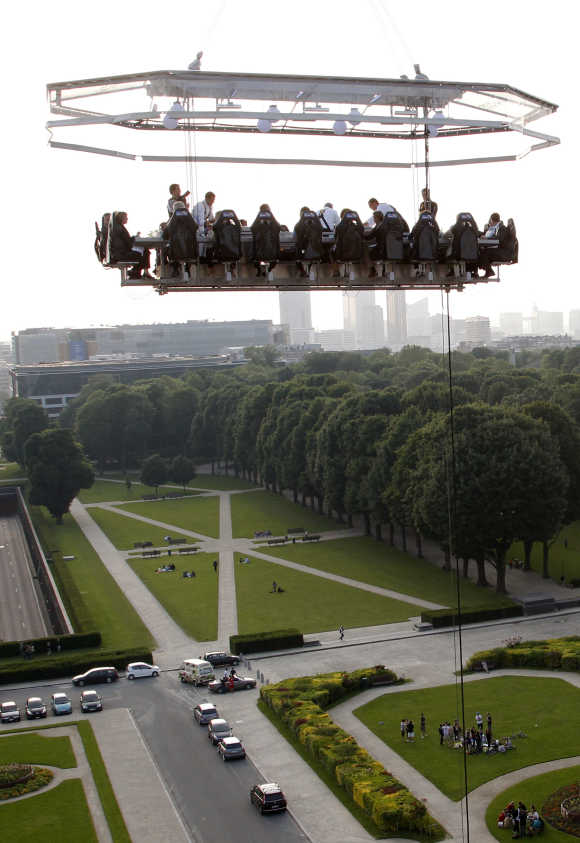 Guests enjoy a 'Dinner in the Sky' on a platform hanging in front of the Cinquantenaire park in Brussels.